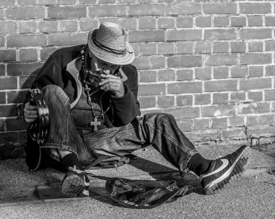 Busker playing harmonica