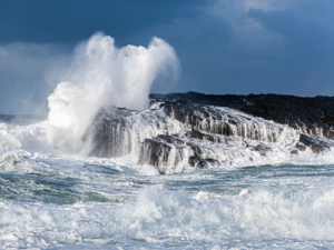 Waves crashing against limestone sea cliff
